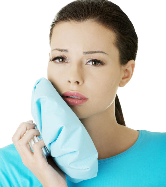 girl holding ice pack to jaw